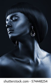 Black Beauty face. Fashion portrait of a dark-skinned beautiful girl with jewerly. Picture taken in the studio on a black background.