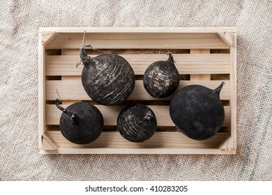 Black beet group in wooden box on rustic fabric background