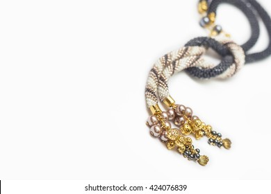Black and beige crocheted necklace with golden pendants