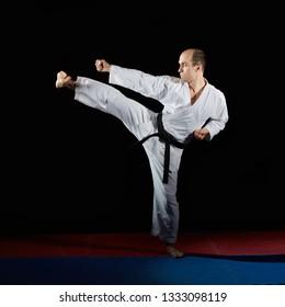Black belt athlete doing formal karate exercises on red and blue tatami