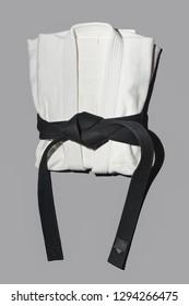 black belt kimono for sambo, judo, jujitsu posing on gray background