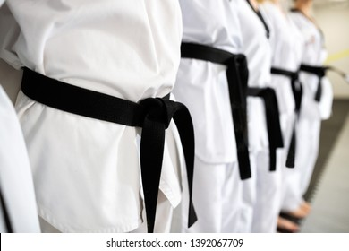 Black belts in close up mode representing devotion and discipline