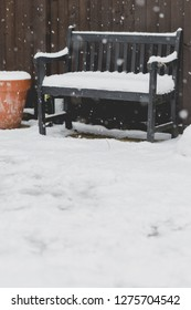 Black bench in garden covered full of snow. Snowflakes fall in foreground. Vertical, low angle perspective
