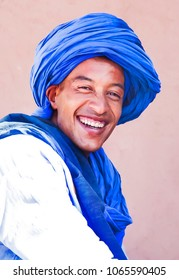 black Berber, in national clothes a man from a Moroccan village wearing a blue headdress with a smile on his face on a pink background