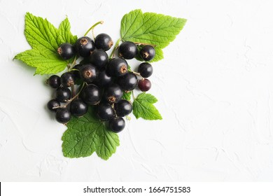 Black berries with green leaves on white texture background with copy space. Top view. Flat lay. Healthy organic blackcurrants. Food for vegetarian