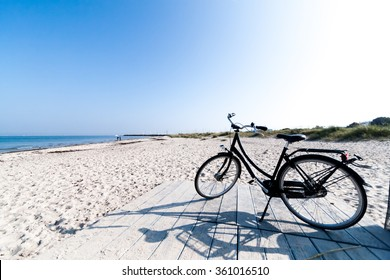 A black bicycle on Marienlyst beach in Helsingor, Denmark, on a beautiful sunny day with clear blue skies. The Danes love to ride their bicycles.