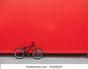 Black bicycle stands nearby red wall, bmx