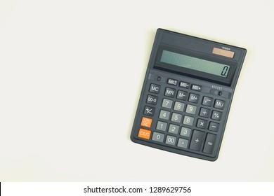 Black big calculator on white background. Toned
