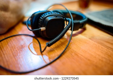 Black big headphones on wooden table front view closeup with blur background