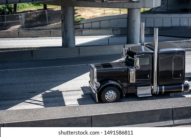 Black big rig American bonnet semi truck with high exhaust pipes transporting commercial cargo on flat bed semi trailer driving on the wide highway road under the bridge in sunny day
