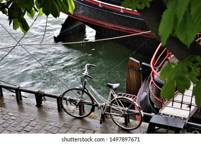 A black bike is parked along a Seine River rail in the middle distance, getting wet with Paris rain, with the edge of a river boat in the background.