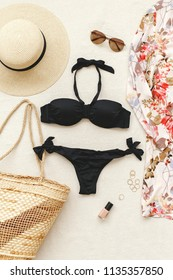 Black bikini swimsuit, floral shirt dress, straw boater hat, wicker beach bag, sunglasses, gold rings on beige background. Woman's swimwear and beach accessories. Flat lay, top view. Beach outfit.