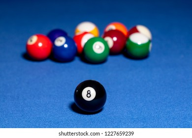 Black billiard ball with number eight. Background out of focus.