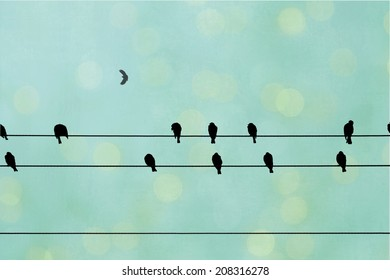 Black birds sit on a wire with an abstract green and yellow textured background.