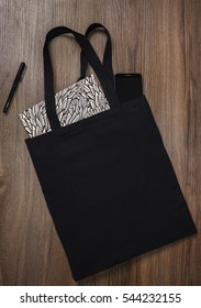 Black blank cotton eco tote bag with smart phone and notebook, design mockup.