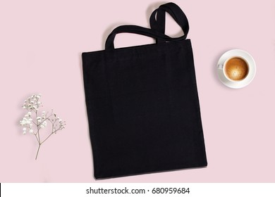 Black blank cotton eco tote bag with baby breath flower and cup of coffee on a pink background, design mockup.