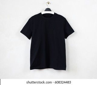Black blank cotton t-shirt hanging center gray empty wall background. Clear label space for business message.