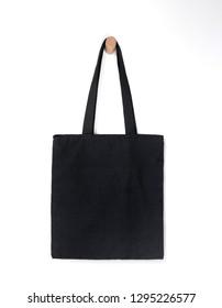 black blank tote bag mock up design on white background hanging on wooden hanger