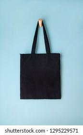 black blank tote bag mock up design on blue background hanging on wooden hanger