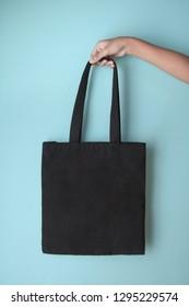 black blank tote bag mock up design on blue background hold by hand