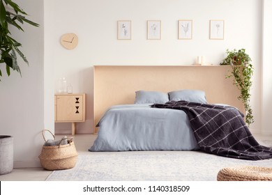 Black blanket on blue bed in natural bedroom interior with posters above bedhead. Real photo