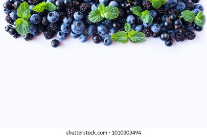 Black and Blue berries isolated on a white. Ripe blueberries, blackberries with mint on white background.  Berries at border of image with copy space for text. Background berries. Top view.