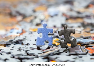 Black and blue puzzle pieces on a pile of jigsaw pieces. Shallow depth of field