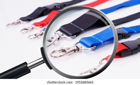 Black and blue and red Lanyards with Metal Lobster Clip magnification through a magnifying glass. On white background.
