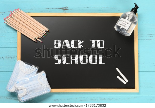 black board with back to school and safety mask and instant hand sanitizer and color pencils