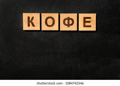 "Black board background with the inscription of ""Coffee"" in Russian language made of wooden cubes with copy space. Top view."