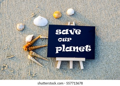 "Black board with text ""save our planet "" on beach sand background"