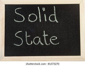A black board with a wooden frame and the words 'SOLID STATE' written in chalk.