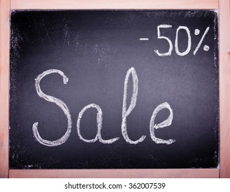 black board with the word: sale with fifty percent discount, is written with white chalk