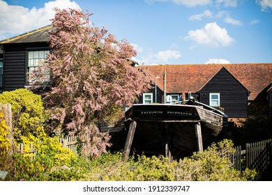 Black boat in front of a rustic village orange roof black barn house with pink flowers tree on the side. Spring Summer time with blue sky. Whitstable, Kent, UK 17 JUNE 2017