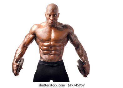 Black bodybuilder posing with round discs. Strong man with perfect abs, shoulders,biceps, triceps and chest. Isolated on white background