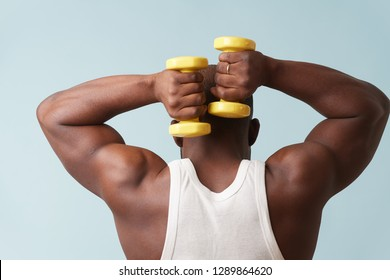 Black bold man in sleeveless white shirt doing overhead tricep extention with two light yellow-collored plastic dumbbells from behind. pale blue background. Tensing biceps. Fitness workout.