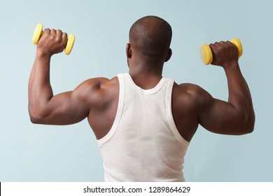 Black bold man in sleeveless white shirt lifting up two light yellow-collored plastic dumbbells from behind. pale blue background. Tensing biceps. Fitness workout.