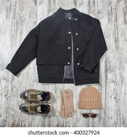 black bomber jacket, sunglasses, beige hat, gloves and military sneakers