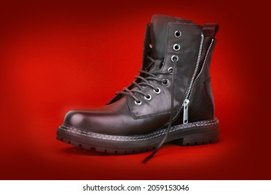 Black boots isolated on red bacground. Steel cap leather boots isolated on red. Black combat men boot, black Military boots at Through use.