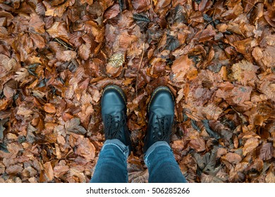 Black boots on the ground which is covered by brown leaves