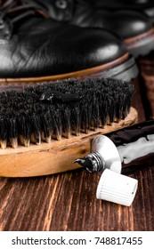 Black boots on wooden background with polishing equipment, brush and polish cream. Macro. Closeup