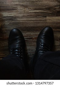 Black boots on wooden floor.
