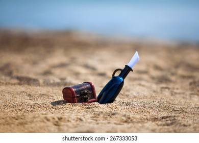 Black bottle and chest on a beach