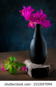 Black bottle used as flower vase with bugambilias flowers in it, on a pieze of brick with leafs of bugambilias at the side, still life photography with dark blue background.