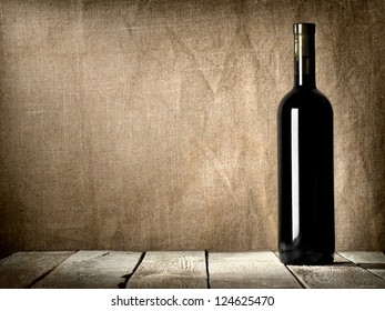 Black bottle of wine on the background of the canvas