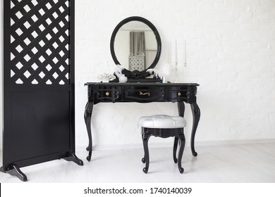 Black boudoir table in a bright room with a white brick wall.