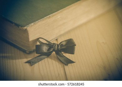 Black bow with ribbon with old book on table ,blur and soft light effice