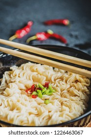 Black bowl of asian instant noodles with hot water and red chili peppers and green onion and chopsticks