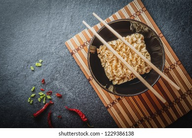 Black bowl of asian instant noodles with and red chili peppers and green onion and chopsticks