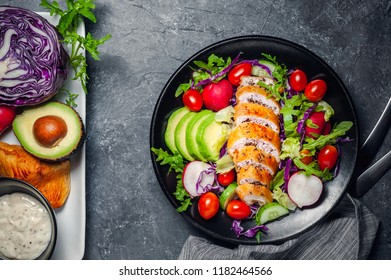 Black bowl with baked chicken breast and salad with fresh vegetables on table background.